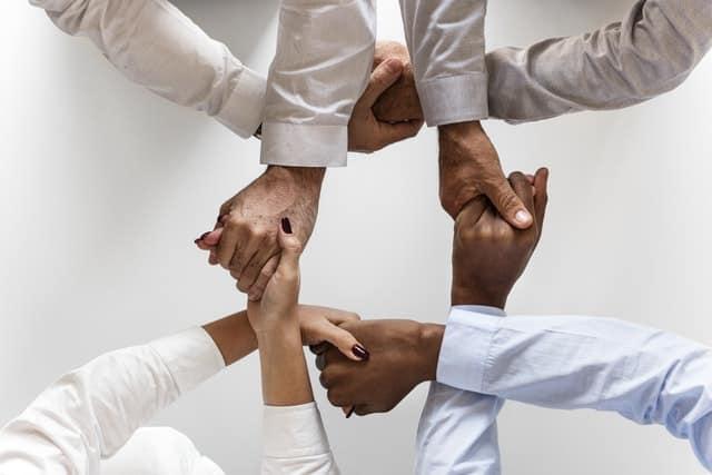 3 personen die elkaar gekruisd de handen geven en zo een patroon vormen